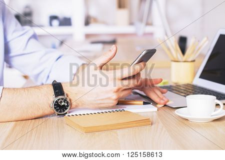 Male hands using smartphone and laptop at desk in office