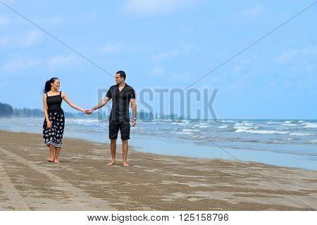 Couple walking on beach.Young happy interracial couple walking on beach and smiling to each other. Asian womanCaucasian man
