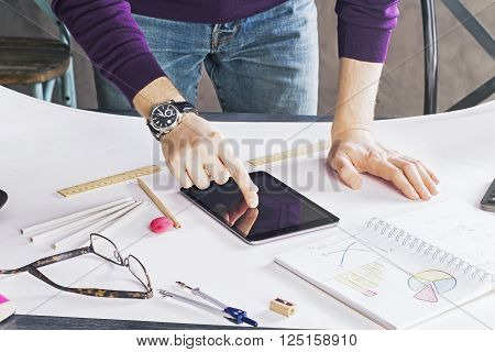 Male using tablet on whatman placed on wooden desktop with many different office tools