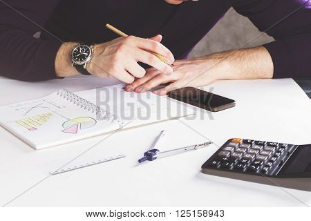 Male drawing business graphs in copybook on white surface with calculator and some other items