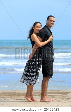 Romantic couple on beach.Young happy interracial couple standing and embracing each other. Asian womanCaucasian man