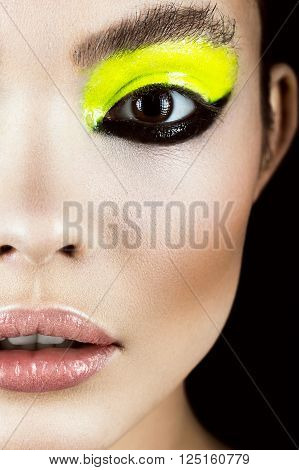 Close-up portrait of girl with yellow and black make-up creative art. Beauty face. Photo shot in studio
