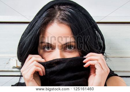 Close up portrait of beautiful young sexy girl with her face covered with black scarf