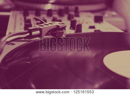 Turntable playing vinyl record with music. Close up macro photo. Professional audio equipment for DJ nightclub or audio enthusiast.