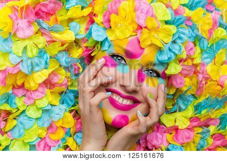 Closeup of young woman face in colorful flower petals. Beauty shot. Face paint.
