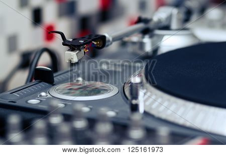 Professional turntable record player. Analog sound equipment for DJ nightclub or audio enthusiast. Focus on the needle