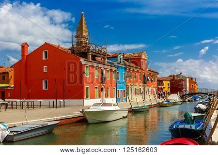 Canal with colorful houses, bridge and church on the famous island Burano, Venice, Italy