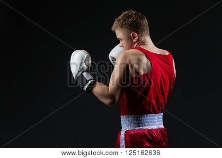 Young boxer in red clothes fighting shadow. Muscular back. Over black background. Copy space.