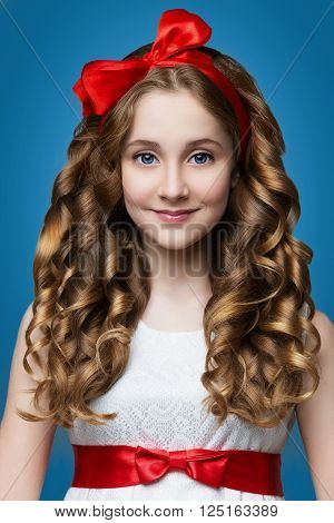 Beautiful teenage girl with curly hair and red rebbon looking like doll. Over blue backgroound.