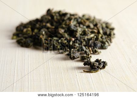 Dried Green Tea Leaves Isolated On Wooden Board Background