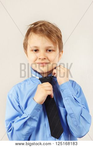 Little cute gentleman tying his tie over bright shirt