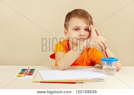 Little artist in an orange shirt going to paint colors