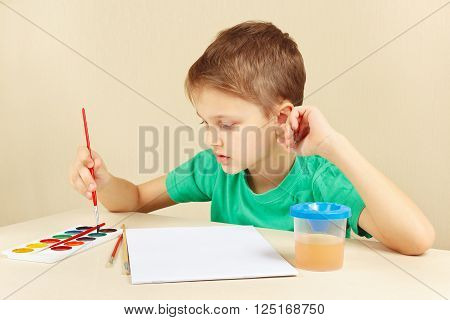 Beginner artist in a green shirt going to paint watercolors