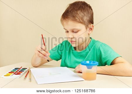 Little artist in a green shirt painting colors