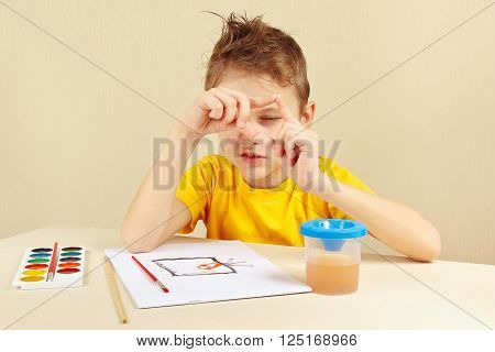 Beginner artist in a yellow shirt painting colors from nature