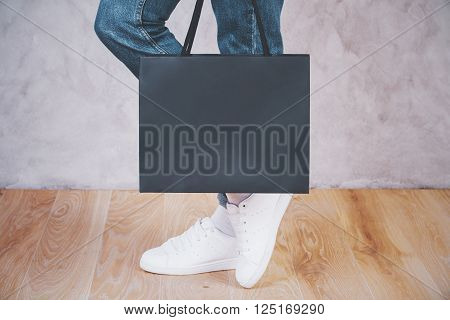 Sideview of female feet with shopping bag on concrete background. Mock up
