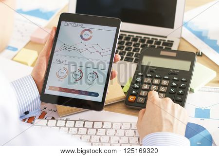 Businessman using calculator and looking at business chart in office