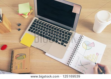 Male hand drawing business graphs on desktop with laptop and office tools