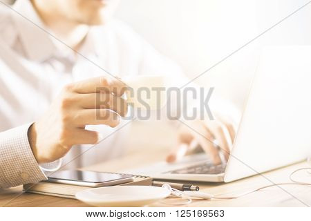 Male drinking coffee while using notebook at wooden desktop with other items