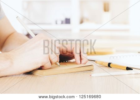 Male hand drawing in aged copybook on wooden desktop. Sideview