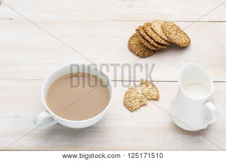 Cup of tea with milk on bright wooden table