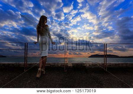 Young beautiful girl in white dress posing at sunset light