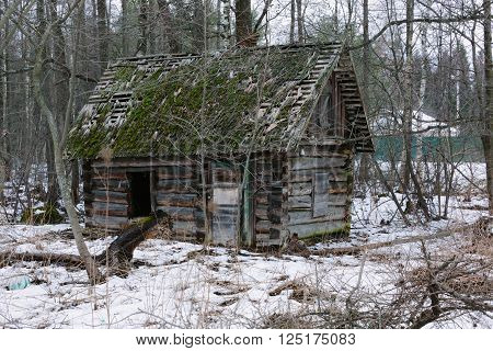 Old small abandoned and ruinous country house in russia. Winter time photo.