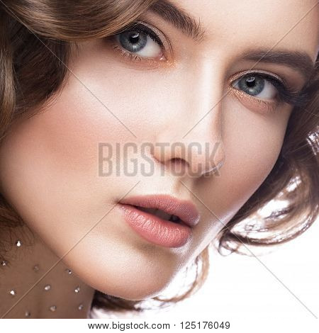 Portrait of a beautiful girl with a gentle make-up, curls and crystals on the body. The beauty of the face. Photos shot in the studio.