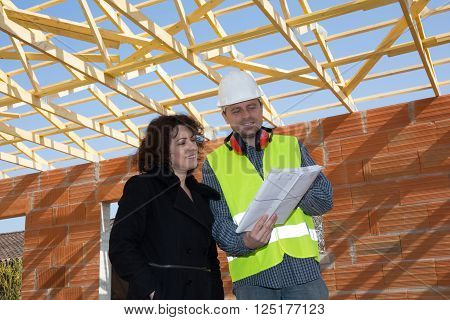 Male architect and mature woman discussing plan on blueprint at construction site
