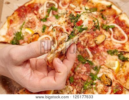 Men hand taking slice of pizza. Top view.