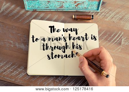 Retro effect and toned image of a woman hand writing on a notebook. Handwritten quote The way to a man's heart is through his stomach as inspirational concept image