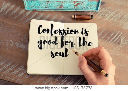 Retro effect and toned image of a woman hand writing on a notebook. Handwritten quote Confession is good for the soul as inspirational concept image