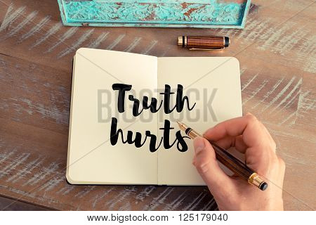 Retro effect and toned image of a woman hand writing on a notebook. Handwritten quote Truth hurts as inspirational concept image