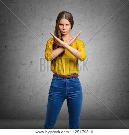 Serious young woman making X sign with her arms to stop doing something. Signs symbols, body language.