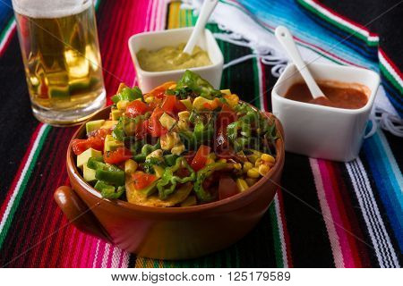 Nachos salad hot sauces and beer over a colored poncho