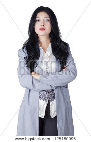 Portrait of a young confident businesswoman standing in the studio with folded arms, isolated on white background