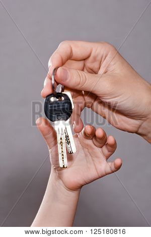 hand of adult hanging house keys to child