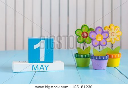 May 1st. Image of may 1 wooden color calendar on white background with flowers. Spring day, empty space for text.  International Workers' Day.