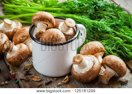 Mushrooms champignons in mug dill and spices on wooden table.