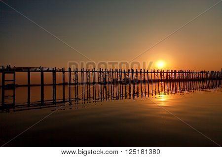 U Bein Bridge at sunset with people crossing Ayeyarwady River Mandalay Myanmar. Wide angle shot