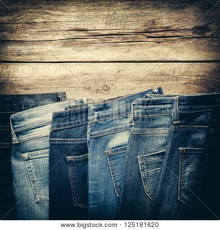 Different jeans on wooden background in store. Retro toned.