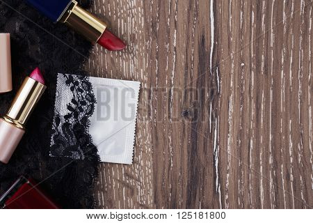 condom and lipstick on a wooden background