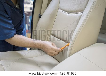 Image of worker hand cleaning the car seat with a brush to remove dust or dirt