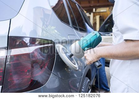 Image of worker hands polish a car body with auto polisher in the workshop