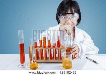 Portrait of cute little scientist wearing lab coat doing experiment, shot in blue background