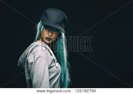 Young woman in hoodie and cap in studio