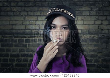 Portrait of naughty teenage girl with long hair and wearing hat enjoy smoking