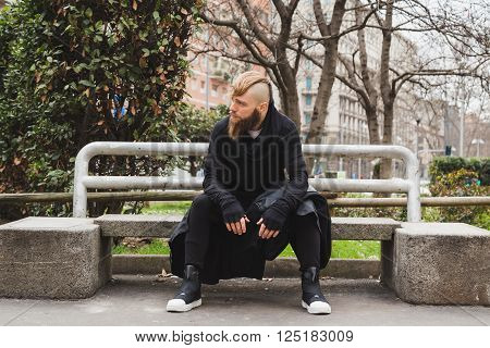 Stylish Bearded Man Sitting On A Bench