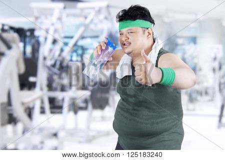 Overweight man drinking water while showing thumb up in fitness center