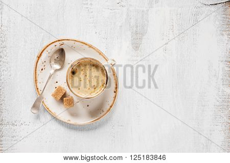 Black coffee with crema in vintage porcelain cup and cane sugar on a light wooden background top view